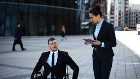 Cripple boss entrepreneur in wheelchair give indications to his businesswoman employe with IPad stock video