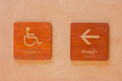Cripple toilet signs on wooden board with arrow pointing way on clay wall. Cripple toilet signs on wooden board with arrow pointing way on clay wall in vintage Stock Photography