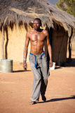 Crippled black African man. Walking barefoot on hot sand of Kalahari desert with native hut in background Stock Photos