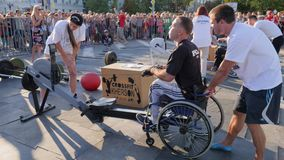 Crippled guy on wheelchair pulls cable at sports training apparatus with trainers on public. Kherson, Ukraine 24 August 2017: crippled guy on wheelchair pulls stock footage