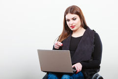 Crippled lady with laptop. Young disabled girl on wheelchair. Health disability internet technology education concept Stock Image
