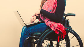 Crippled person with laptop. Young disabled female surfing on web. Internet technology education disability concept Stock Photography