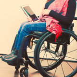 Crippled person with tablet. Young disabled female surfing on web. Internet technology education disability concept Stock Photography