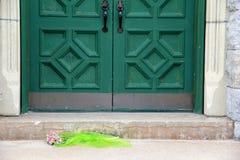 Cripta del cementerio con el ramo de la flor delante de puertas verdes pesadas Foto de archivo libre de regalías