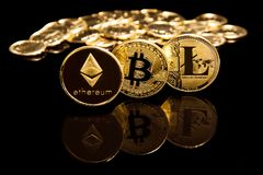 Criptocurrency concept of bitcoin litecion and ethereum coins on black mirror surface next to golden coins stock photo