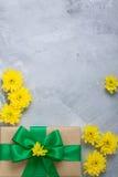 Crisântemos do amarelo do ramalhete da caixa de presente no backgrou concreto cinzento Foto de Stock