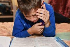 Cris d'adolescent tout en résolvant des devoirs difficiles d'école dans une chambre sur un lit photo libre de droits