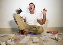 Cris soumis à une contrainte fous d'homme inquiétés tenant la dette domestique de comptabilité de paiements de calculatrice ayant Photos stock