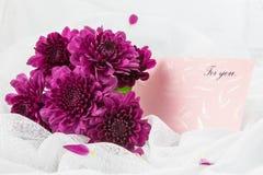 Crisantemos púrpuras con la tarjeta de papel Imagenes de archivo