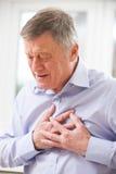 Crise cardiaque de souffrance d'homme supérieur à la maison photo libre de droits