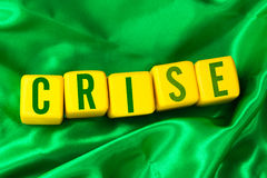 Crise (Crisis in Portuguese) written on yellow cube on green background Stock Photo