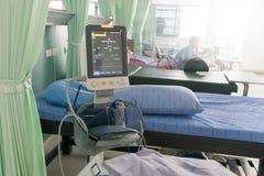 Crise de patients se situant au coeur de tension artérielle de machine d'électrocardiogramme de lit Image libre de droits