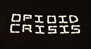 A crise do opiáceo soletrou para fora com comprimidos brancos em um fundo preto Imagens de Stock