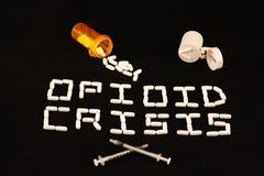 A crise do opiáceo soletrou para fora com comprimidos brancos em um fundo preto com os comprimidos derramados da prescrição e um  Fotografia de Stock Royalty Free