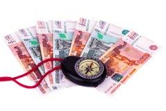 Crise financeira: um compasso e um dinheiro em um fundo branco Imagens de Stock Royalty Free