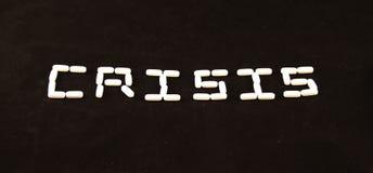 A crise soletrou para fora com comprimidos brancos em um fundo preto Fotografia de Stock Royalty Free