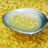 Crisis. Alphabet pasta letters forming word crisis on a spoon with soup Royalty Free Stock Photography