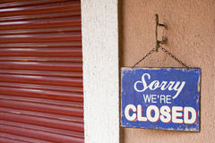 Crisis. Vintage metal closed sign next to a closed blind, as a concept of crisis Royalty Free Stock Image