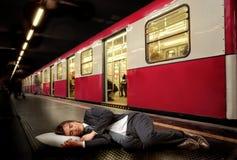 Crisis. Businessman sleeping on the subway floor Royalty Free Stock Image