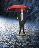 Crisis. A man in a suit on two rocks in a rain storm and in water. Metaphor for a business man weathering the storm or a crisis at work Royalty Free Stock Photos