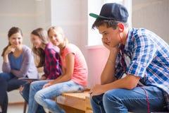 Crisis of adolescents. Boy teenager sad alone sitting in school corridor stock photography