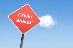 Crisis ahead. On a road sign Royalty Free Stock Photo