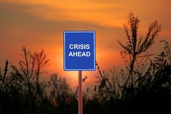 Crisis Ahead concept. A sign warning a Crisis Ahead concept- in a sunset background Royalty Free Stock Image