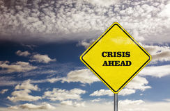 Crisis ahead road sign and blue sky Stock Photo