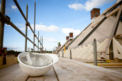 Crisis building industry. Empty building site with left helmet on scaffold Stock Photography