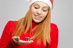 Crisis Christmas. Beautiful red hair woman holding a small Christmas present. Girl in red with Santa hat looking down smiling Stock Images