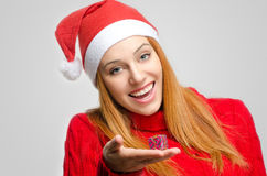 Crisis Christmas. Beautiful red hair woman holding a small Christmas present. Girl in red with Christmas Santa hat smiling Royalty Free Stock Photo