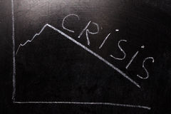 Crisis Concept. Crisis on Dark Background.chalk on a blackboard Stock Photo