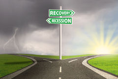 Crisis concept with recession and recovery signpost. Road sign with recession and recovery words pointing at the option highway royalty free stock photos