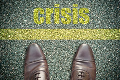 Crisis. Concept signage in the road with feet and yellow line  - crisis Royalty Free Stock Photos