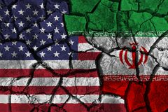 Crisis and confliction concept of america and iran . flags on cracked ground background stock image