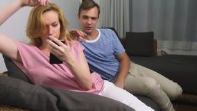 Crisis de los pares El hombre y la mujer pasan la tarde en la sala de estar en el sofá Una mujer utiliza su teléfono e ignora almacen de video