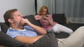 Crisis de los pares El hombre y la mujer pasan la tarde en la sala de estar en el sofá la mujer utiliza el teléfono, el hombre es metrajes