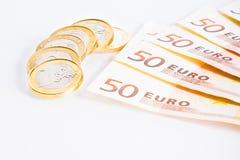 Crisis of eurozone, euro coins on 50-euro banknotes. Crisis of eurozone, detail of some euro coins on 50-euro banknotes on white background stock images