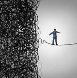Crisis Management. Business concept as a tightrope walker walking out of a confused tangled chaos of wires breaking free to a clear path of risk opportunity as Royalty Free Stock Images