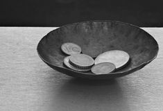 Crisis, Poverty. Tiny bowl with coins, indicates the actions of donating or receiving. Also means Poverty, Charity, Begging, Earnings stock photography