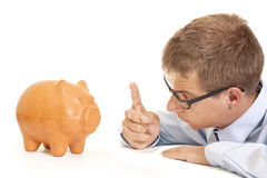 Crisis time. Business man in crisis time threaten the piggy bank Stock Photos