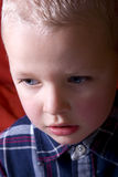 The crisis time. The little boy is sad. The facial portrait of boy on the red background Stock Photo