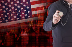 Crisis in USA with businessman holding a stethoscope. Crisis in USA shares fall graph on United States of America flag with businessman hand holding a Royalty Free Stock Photo