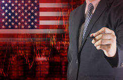 Crisis in USA with businessman writing on the screen. Crisis in USA shares fall graph on United States of America flag with businessman writing, drawing on the Royalty Free Stock Photo