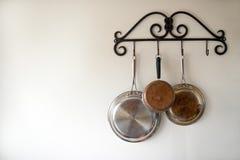 Crisoles y cacerolas en una pared Imagen de archivo libre de regalías