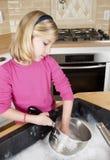 Crisoles y platos de la limpieza de la niña Imagen de archivo