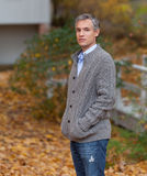 Crisp Autumn Day. A handsome man with gray hair poses in front of a beautiful colorful fall / autumn background Royalty Free Stock Photo