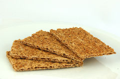 Crisp bread. Four slices of healthy brown delicious rye crisp bread on a plate. Image isolated on white studio background royalty free stock photo
