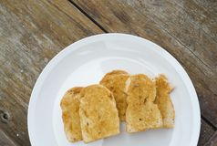 Crisp bread garlic. In white plate on wooden board Stock Image