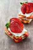 Crisp bread with goat cheese and strawberries Stock Image